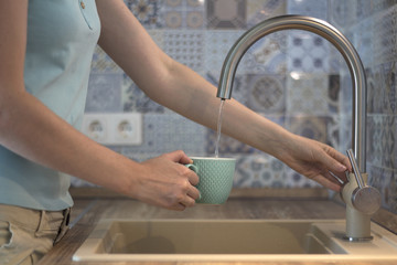 The young woman pours water from the kitchen faucet