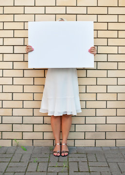The woman hid her face behind an empty banner on the street against a yellow brick wall.