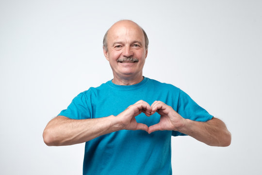 old caucasian man in blue t-shirt making out of hands heart.