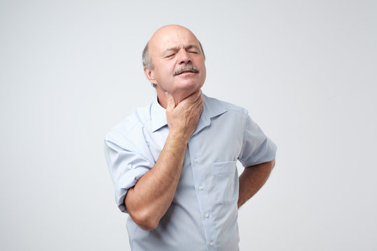 Mature man has a terrible pain in throat because of flu.