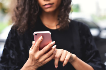 Closeup image of a beautiful mixed race woman holding, using and looking at smart phone with feeling happy.