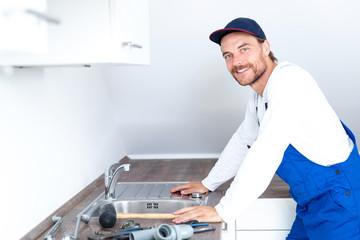 Installateur / Klempner positiv lächelnd bei der Arbeit in einer Küche