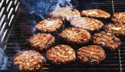Preparing delicious hamburgers on the outdoor grill for family lunch. Conceptual picture of grilled burgers at fire flame. Hamburger patties turn over on the grill.