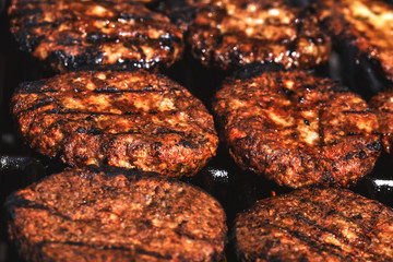 Appetizing hamburgers grilled on the outdoor grill in front of american restaurant. Conceptual picture of finishing cooking a black burger. Hamburger cutlets turn over on the grill.