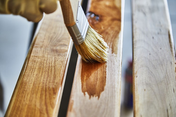 Paint Brush in a can of varnish in preparation to stain the wood slats