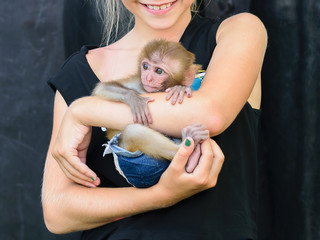 The girl carefully holds a small monkey on her hands.