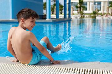 Portrait of smiling Caucasian boy spending time in pool at resort.