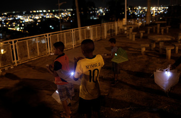 Kids hold kites with LED lights during the Pipas pela Paz (Kites for Peace) event in the Alemao slums complex in Rio de Janeiro