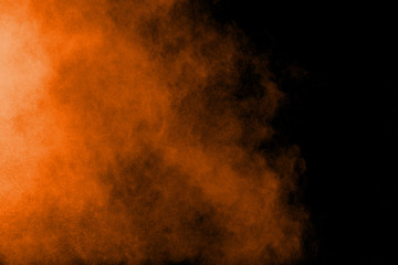 Abstract orange powder explosion on black  background. Freeze motion of orange  dust particles splash.