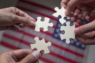 Group of business people assembling jigsaw puzzle and represent team support and help concept with American flag background.