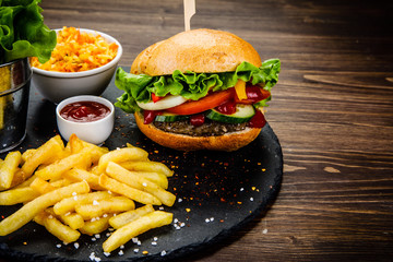 Tasty burger with chips served on stone plate