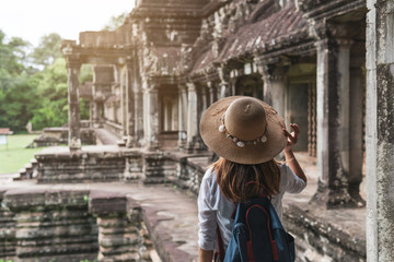 Young woman traveler visiting at Angkor Wat complex, Khmer architecture heritage in Siem Reap, Cambodia