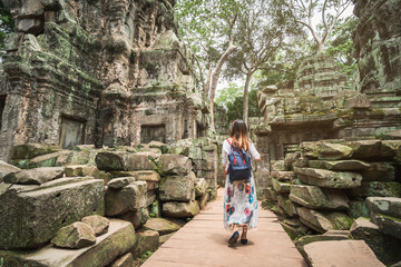Young woman traveler visiting in ta prohm temple at Angkor Wat complex, Khmer architecture heritage in Siem Reap, Cambodia