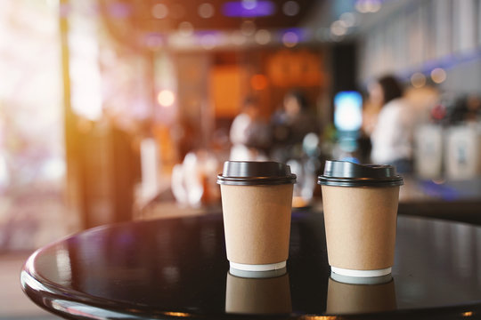 Take away two coffee cups empty blank copy space for your design text or banner of brand on the table in the cafe with light