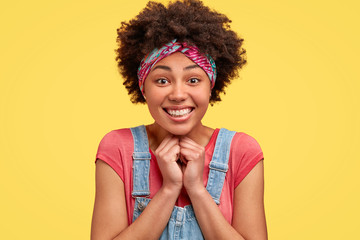 Studio shot of cheerful African American female keeps hands together near chin, smiles broadly, anticipates for surprise prepared by friends on her birthday, isolated over yellow background.