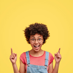 Photo of joyful African American female with positive smile, crisp hair, points above with index fingers, has glad expression, poses against yellow background. Happy dark skinned woman indoor