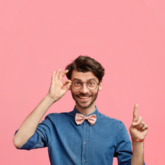 Wall Mural - Positive elegant young male with trendy hairstyle and stubble, dressed in denim shirt with bowtie, has joyful expression, points upwards against pink background, keeps hand on rim of spectacles