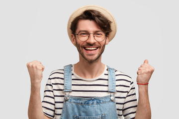 Good looking positive male farmer raises clenched fists, feels satisfied and excited, achieves great success in agricultural sphere, wears casual overalls, striped sweater, straw hat, has broad smile