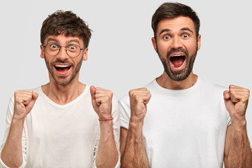 Wall Mural - Portrait of happy overjoyed bearded guys clench fists and exclaim joyfully, express positiveness, rejoice success, dressed in white casual t shirts, stand next to each other. Winning concept