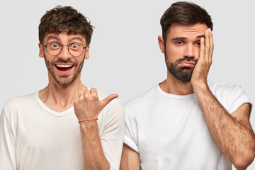 Wall Mural - Positive Caucasian young male with dark hair, points with thumb at his discontent companion who regrets something, keeps hand on cheek, express different emotions, isolated over white background