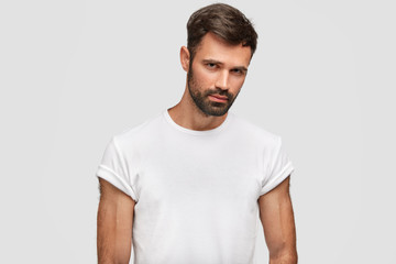 Serious muscular young male with dark stubble, hair, dressed in casual white t shirt, has muscular body, listens attentively something, isolated over white background. Unshaven guy stands indoor