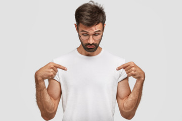 Photo of hipster male with thick beard and mustache, dressed in white clothing, points with index fingers at white tshirt, keeps head down, shows blank space on outfit for your advertising content
