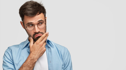 Studio shot of handsome pensive male holds chin, thinks about something, dressed in blue shirt, stands against white background with free space for your promotional content. Thoughtful bearded man