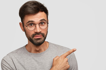 Photo of handsome European male with thick beard and mustache, points with fore finger aside at free space for your promotional content, wears round spectacles and grey t shirt. Advertisement