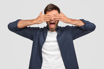 Handsome male covers eyes with both hands, keeps mouth widely, has stubble, dressed in shirt, waits for surprisement, isolated over white background. Young bearded man peecks through fingers.
