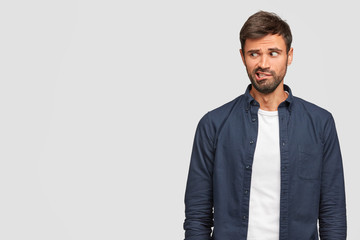 Curious bearded young European male looks nervously, purses lips and gazes suspiciously aside, dressed in casual clothes, stands alone against white background with copy space for your promotion