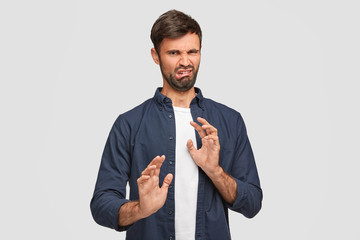 Negative facial expressions and people concept. Unhappy displeased young male frowns face with discontent look, feels aversion towards something, gestures indoor, stands against white background