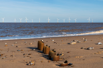 North sea coast in Caister-on-Sea, Norfolk, England, UK - with a wave breaker at the beach and wind turbines in the background