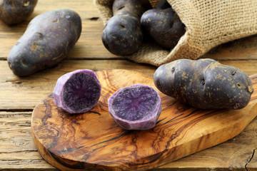primo piano patate blu crude su sfondo tavolo di cucina