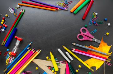 School supplies on blackboard background, top view. Back to school and Education concept.  Flat lay, copy space