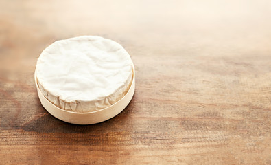 Cheese camembert on wooden desk, top view. Soft creamy cheese Brie with copy space.
