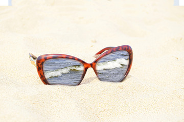 Sunglasses are on sand. The image of the sea is in a frame of sunglasses. Glass lenses are inserted into a casing of color of a tiger.