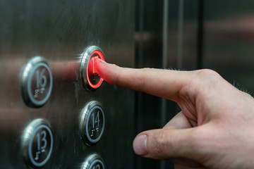 the man presses the elevator button with the red light.