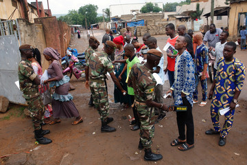 Malian soldiers carry out checks as people wait at a polling station before the polls open during a presidential run-off election in Bamako