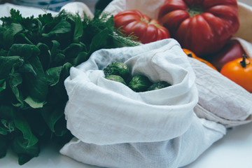 Eco friendly canvas grocery bag with cucumbers, tomatoes and greens. Local market vegetables in the reusable totebag