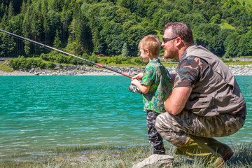 father and son fishing together on a mountain lake
