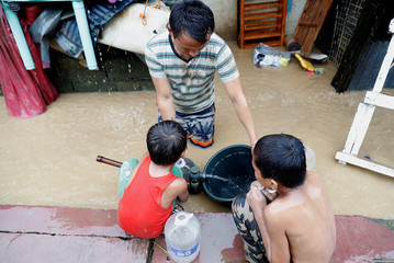 Residents fetch water from a submerged water pump along a flooded sidewalk after continuous monsoon rains in Marikina