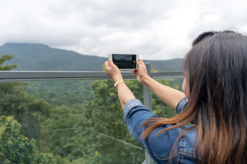 The girl is photographing a mountain on the skyline.