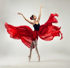Ballerina. Young graceful woman ballet dancer, dressed in professional outfit, shoes and red weightless skirt is demonstrating dancing skill. 