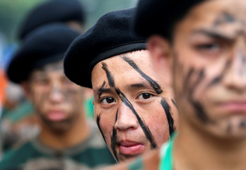 A schoolboy with his face painted looks on as he waits to take part in a full dress rehearsal for India's Independence Day parade in Kolkata