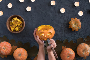 Top view of woman carves face of a jack-o'-lantern on orange halloween pumpkin, flat lay on black background