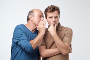 Fototapeta Senior man sharing secret or whispering gossips into his son ear. Telling family secret concept obraz