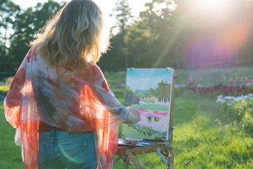 The painter paints oil paintings in the garden at sunset