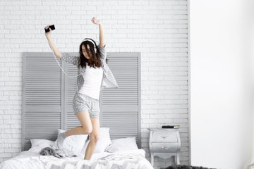 Happy funny brunette woman female girl with curly hair wears grey pajamas sleepwear with hearts and headphones and smartphone listening to music dancing on bed in light interior room. Morning concept