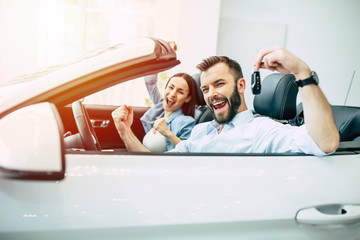 Happy young couple chooses and buying a new car in the dealership.