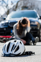 Bicycling helmet on the asphalt after accidental collision between the bicycle of a sorrowful young woman and a 4x4 car in the city
